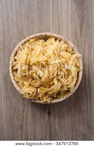 high angle view of an earthenware bowl with cooked sauerkraut, german finely cut fermented cabbage, on a wooden surface