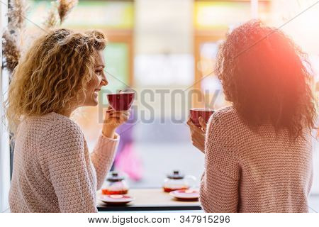 Two Multi Ethnic Girls Friends Enjoying Tea Together, Meets In A Coffee Shop Sit At A Table Counter
