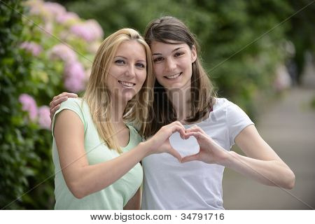 lesbian couple forming heart shape with hands