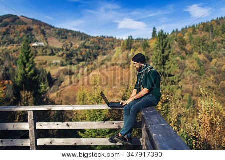 Bearded Businessman Sits On Railing And Works On Laptop. Freelancer Hipster On Vacation In Mountains