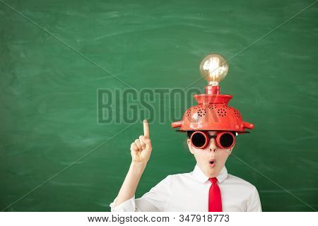Happy Child In Classroom. Funny Kid With Light Bulb Against Green Chalkboard Background. Innovation