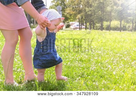 Mom Learning Baby Daughter To Walk, First Steps In Park At Summer Warm Day With Barefooted Legs In G