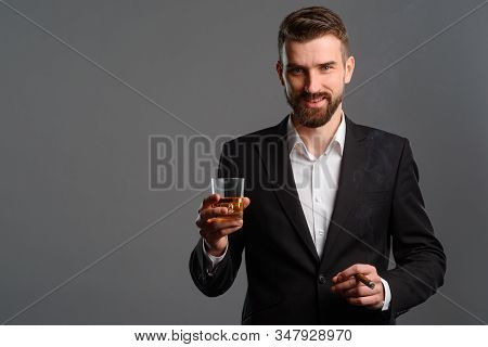 A Man In Classic Outfit Drinking Finest Old Whisky And Smoking Expensive Cigar