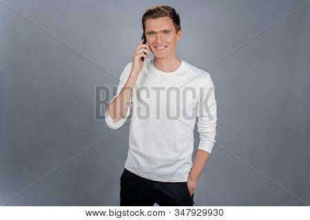 Image Of Positive Man 30s In Wearing Wite T-shirt Speaking On Black Smartphone Isolated Over Gray Ba
