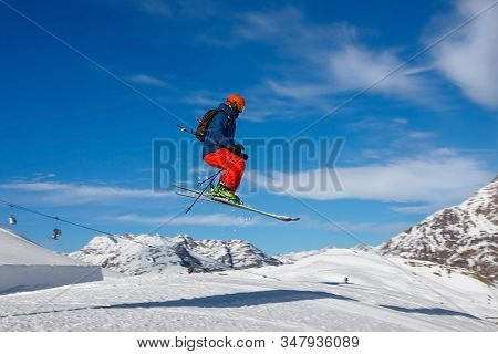Male Skier Jumps In Snow Park In The Snowy Mountains Against The Blue Sky. Livigno, Italy
