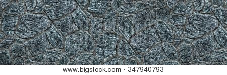 Wide Blue Granite Stone Wall Texture. Rough Rock Masonry Surface. Dark Widescreen Background