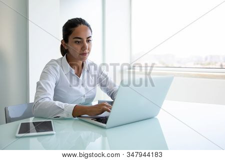 Serious Young Businesswoman Using Laptop In Office. Focused Young Businesswoman Sitting At Desk And