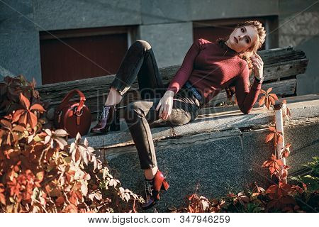 Young Fashionable Beautiful Girl In A Black Jeans And With A Dark Red Bag. Portrait Shooting Of A St