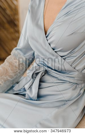 A Girl In A Silk Robe Meets Morning. Woman Unties The Ties Of A Blue Robe. Girl In Silk Underwear.