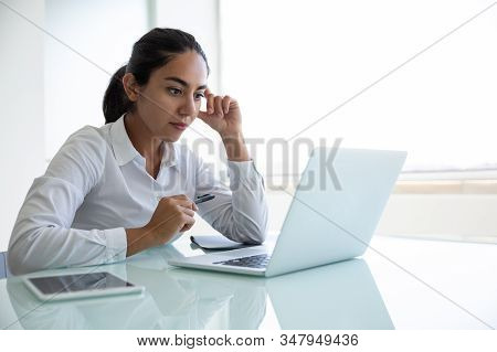 Concentrated Young Businesswoman Using Laptop In Office. Focused Young Businesswoman Sitting At Desk