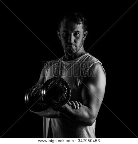 Black And White Portrait Of A Man In A T-shirt With Dumbbell In Hand. Muscular Athlete Is Training.