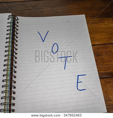 Vote, Handwriting  Text On Paper, Political Message. Political Text On Office Agenda. Concept Of Dem