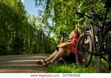 A Tired Male Cyclist Sits On The Side Of The Road And Drinks Water From A Bottle.