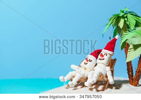 Two Marshmallow Snowmen In Love Are Sitting On Deckchairs On A Sandy Beach. Christmas Holidays On Th