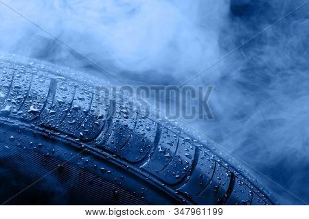 Car Tire Covered With Water Drops In The Fog. Toning In Trendy Color 2020 Classic Blue.