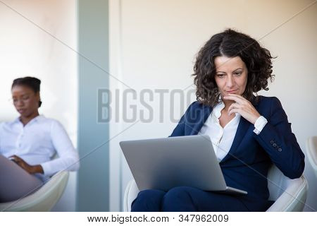 Concentrated Businesswoman Using Laptop Computer. Middle Aged Businesswoman Using Laptop Computer Wh