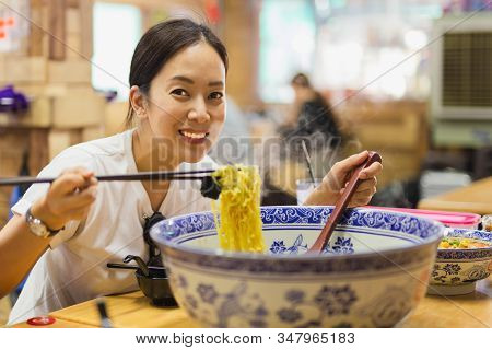 Happy Smiling Woman Eating Big Bowl Of Noodle Soup In Chinese Restaurant.