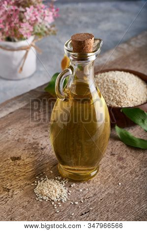 Sesame Oil In Glass Bottle And Sesame Seeds On Wooden Background Vertical