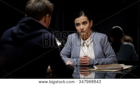 Woman Police Officer Interrogating Male Suspect In Dark Room, Mistrust, Equality
