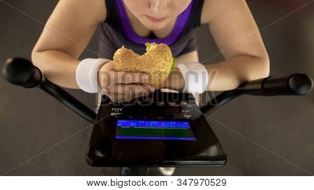 Corpulent Female Eating Fatty Burger While Riding Stationary Bike, Fast Food