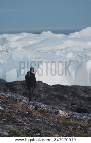Greenland Tourist Man Explorer Overlooking Icefjord In Ilulissat. Travel In Arctic Landscape Nature