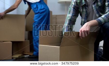 Man Unboxing Things In New Apartment, Moving Company Worker Bringing Boxes