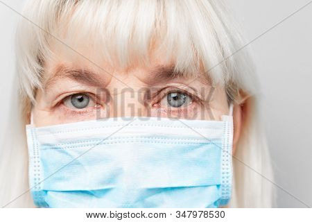 Adult Woman In A Medical Mask Looks At The Camera. Virus Protection. Stop Virus Infection. Novel Cor