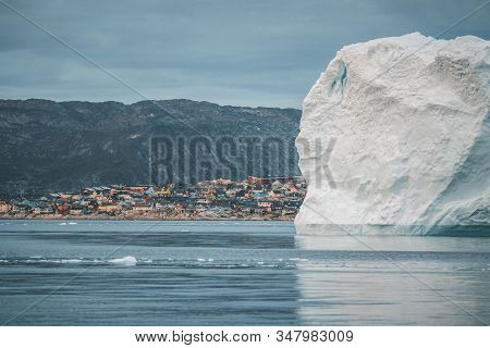 Greenland Glacier With Sea Ice And Huge Iceberg In Front Of Arctic City Of Ilulissat. Glacial Landsc