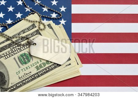 Army Identification Medallions And Dollar Bills On United States Flag. Military Pension, Salary In T