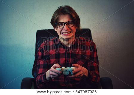 Focused teen boy playing video games late night seated in his chair. Angry and furious guy nerd wearing glasses, holding the joystick console, screaming and clenching teeth, trying to win the game. poster