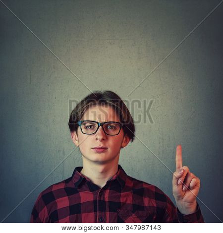 Confused Adolescent Guy, Wearing Eyeglasses Gesturing, Pointing Index Finger Up, Perplexed Expressio