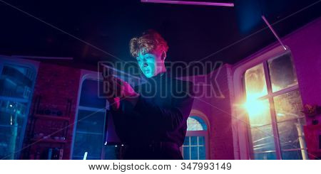 Attented. Cinematic Portrait Of Stylish Redhair Man In Neon Lighted Interior. Toned Like Cinema Effe