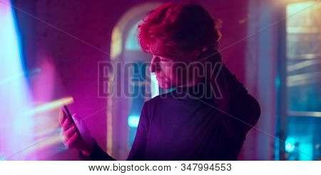 Thoughtful. Cinematic Portrait Of Stylish Redhair Man In Neon Lighted Interior. Toned Like Cinema Ef