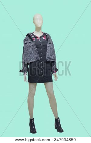 Full Length Female Mannequin Wearing Jeans Jacket And Pinafore Dress, Isolated On Green Background.
