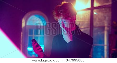 Astonished. Cinematic Portrait Of Stylish Redhair Man In Neon Lighted Interior. Toned Like Cinema Ef