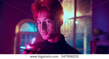 Recording Voice Message. Cinematic Portrait Of Redhair Man In Neon Lighted Interior. Toned Like Cine