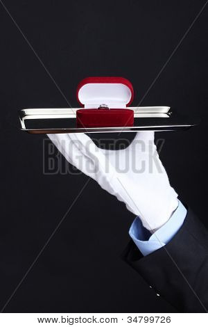 Man's hand holding ring in box on tray