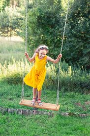 Beautiful Teen Girl Standing On Swing At Summer Day, Happy Childhood Concept