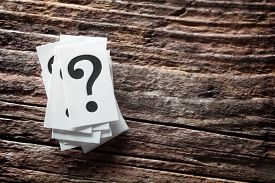 Question mark heap on wood background concept for confusion, question or solution