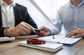 Car Rental And Insurance Concept, Young Salesman Giving Car's Key To Customer After Sign Agreement C