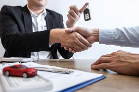 Car Rental And Insurance Concept, Young Salesman Shaking Hands After Finishing Up A Collaboration Di