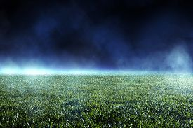 Empty Green Turf On A Sports Field In A Soccer Or Football Stadium Illuminated By Distant Spotlights