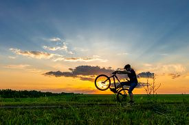 Silhouette Of A Male Cyclist Riding A Bicycle With A Raised Front Wheel. Cyclist In A Helmet On A Su