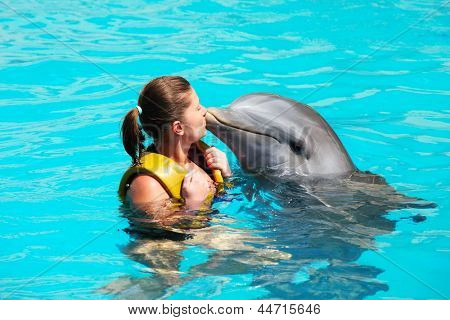 A picture of a young woman kissing a dolphin in a turquise water