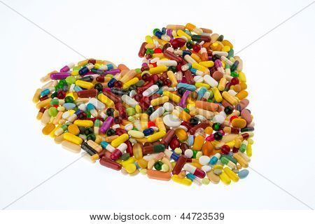 colorful tablets arranged in heart shape, symbol photo for heart disease, medication and pharmaceuticals