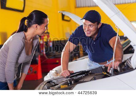 trustworthy auto technician talking to female customer in garage