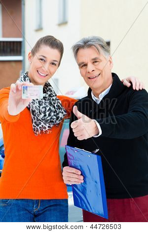 Driving school - Young woman has passed her driving test and proudly holding her driver license, the driving instructor is standing next to her