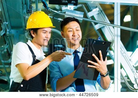 Worker or production manager and owner, ceo or controller, look on a Clipboard in a factory