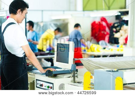 Worker or production manager at a screen of a large machine in a textile factory in Asia