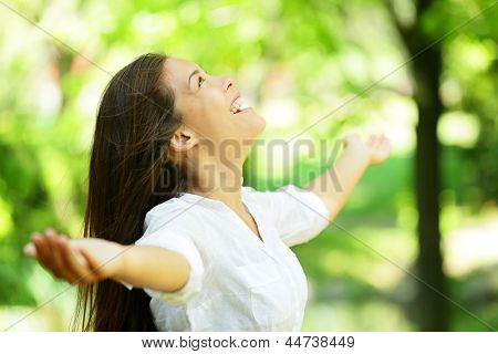 Attractive young woman rejoicing in a spring or summer garden standing sideways with her arms outstretched and her head raised to the heavens enjoying the freshness and beauty of nature